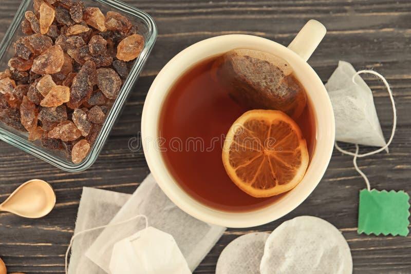 Saquinhos de chá e copo com a bebida quente na tabela foto de stock