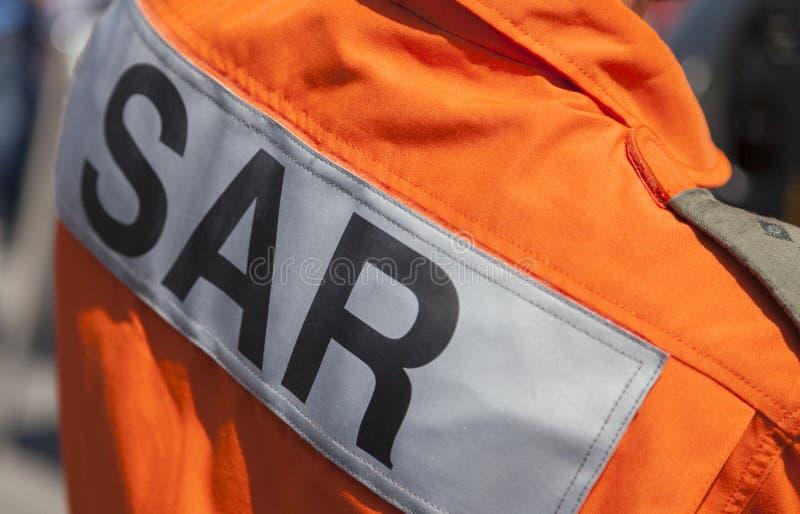 SAR搜寻并且抢救在一名飞行员的商标从抢救直升机 库存图片