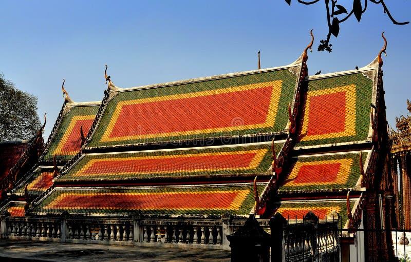 Saraburi, Thailand: Vihan Hall at Wat Phra Phutthabat. Saraburi, Thailand - January 8, 2013: Orange, yellow, and green interlocking gabled roofs with Chofah royalty free stock photography