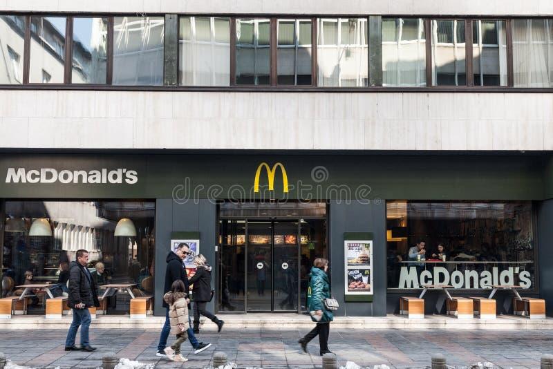 SARAJEVO, BOSNIË - FEBRUARI 17, 2018: Voetgangers die voor een Mc Donald ` s restaurant op de hoofdstraat van Sarajevo overgaan royalty-vrije stock fotografie