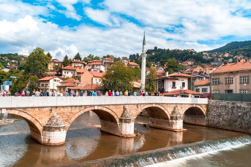 Miljacka River and Bridges in Sarajevo. SARAJEVO, BOSNIA - AUGUST 3, 2019 : Houses near Miljacka river and bridges. The old town is most popular place for royalty free stock images