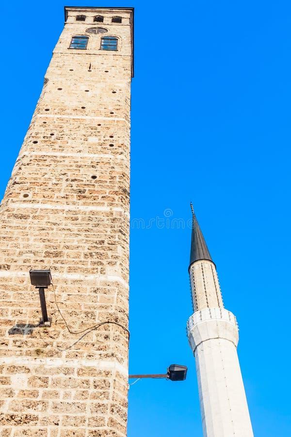 Sarajevo Bosnia y Hercegovina Vista del alminar de la mezquita de Begova al lado de la torre de reloj islámica del kula de Sahat fotografía de archivo