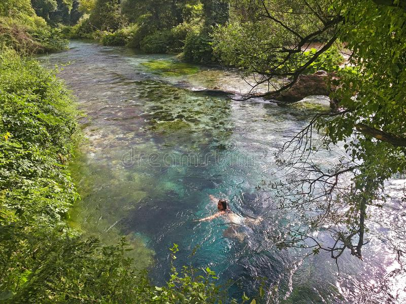 Sarande, Albania – July 19, 2018: Young girl is swimming in the Blue Eye Syri i Kalter - water spring. stock photo