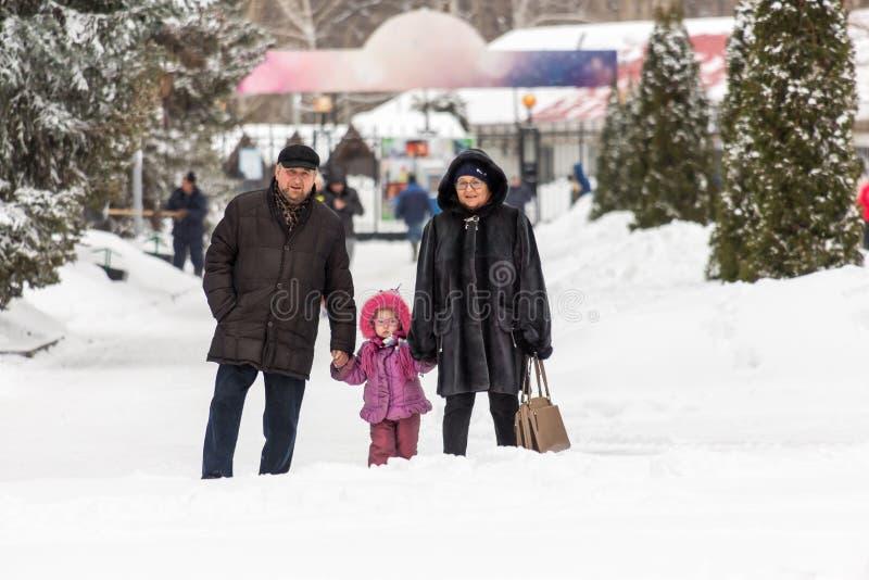Saratov/Rússia - 8 de março de 2018: As avós e a neta que andam na cidade estacionam Dia de inverno fotos de stock royalty free