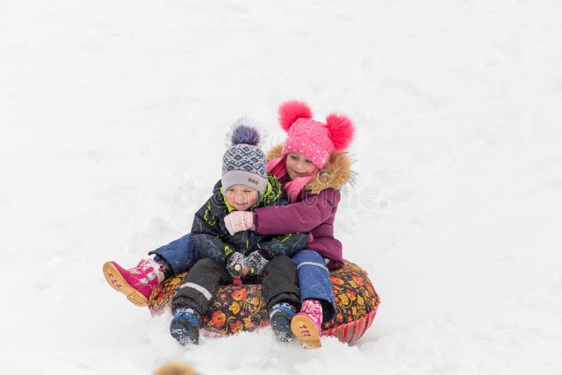Saratov/Rússia - 8 de março de 2018: Passeio das crianças com uma corrediça do gelo Férias do inverno Atividade ao ar livre Dia d imagens de stock royalty free
