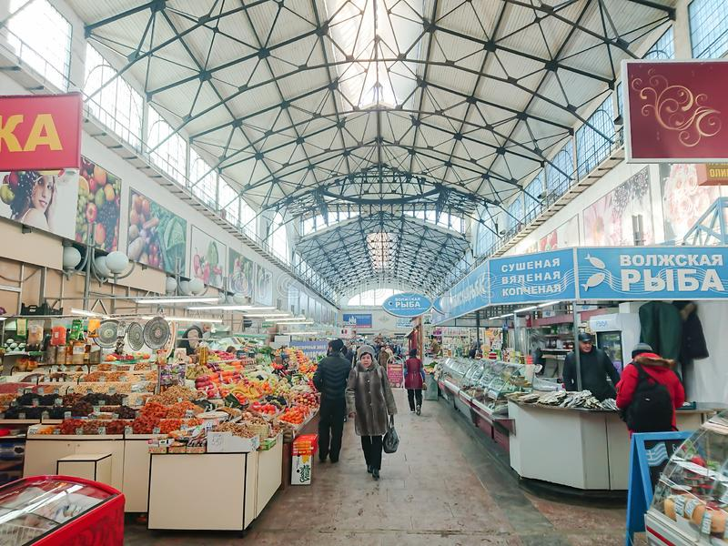 Saratov / Russia - January 26, 2019: Covered market. Ancient building, built in 1916. Sale of various food products. People, buyers and sellers royalty free stock photography