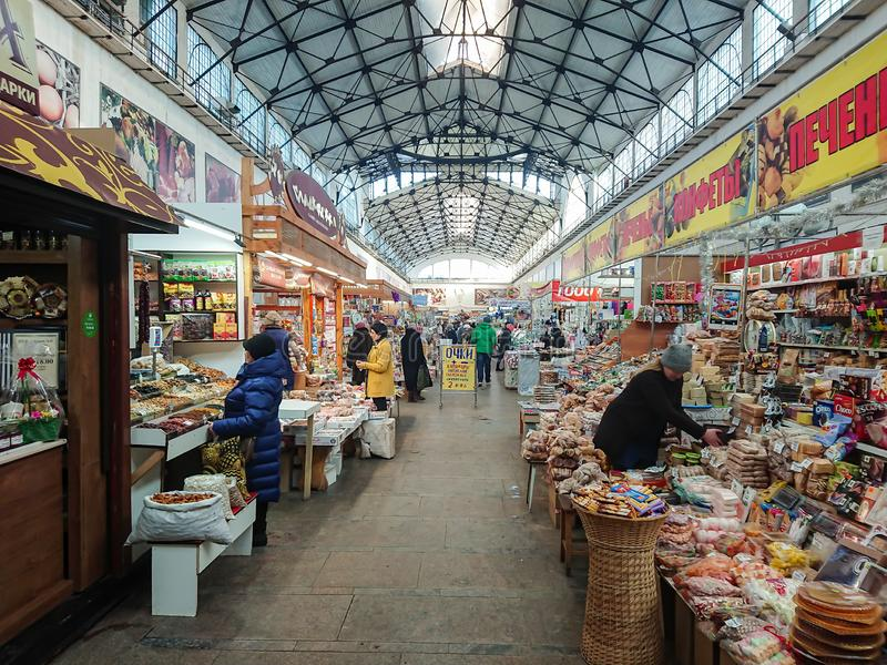 Saratov / Russia - January 26, 2019: Covered market. Ancient building, built in 1916. Sale of various food products. People, buyers and sellers stock photography