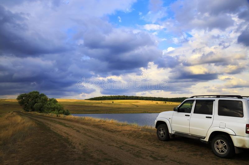 Saratov, Russia - 06/28/2019: Travel, tourism by car SUV. White UAZ Patriot in the evening on the nature on the road against the royalty free stock images