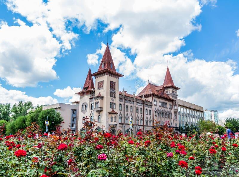 Saratov statkonservatorium Öppnades i 1912 Ryssland Blommande rosor i förgrunden Moln på en blåttsky royaltyfri fotografi