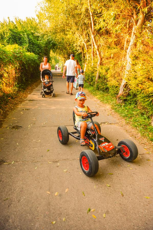 Boy on pedal cart. Sarbinowo, Poland - August 9, 2018: Boy riding a pedal go kart on a path with walking people on a sunny day by the seaside royalty free stock photography