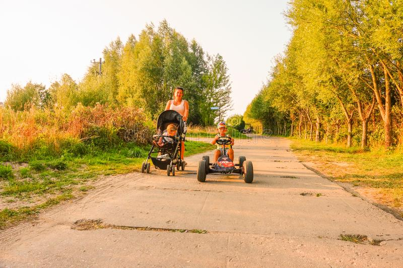 Child on cart. Sarbinowo, Poland - August 9, 2018: Boy sitting in a pedal go kart on a road at the seaside on a warm summer day. Woman with baby buggy following stock image