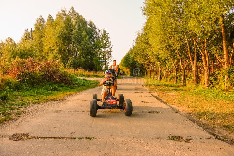 Boy on cart. Sarbinowo, Poland - August 9, 2018: Boy sitting in a pedal go kart on a road at the seaside on a warm summer day. Woman with baby buggy following stock photo