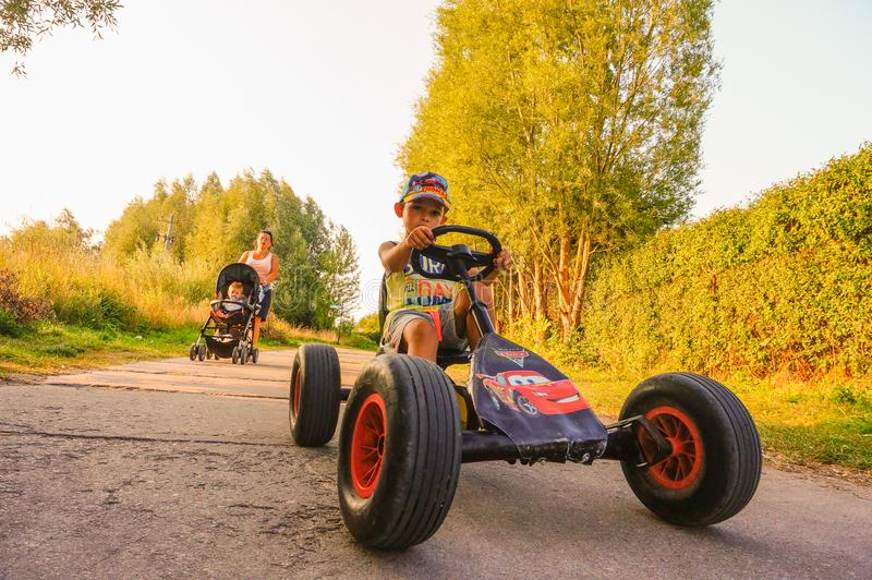 Child on cart. Sarbinowo, Poland - August 9, 2018: Young boy steering a pedal go kart on a small road. Woman with baby buggy walking behind the child royalty free stock image