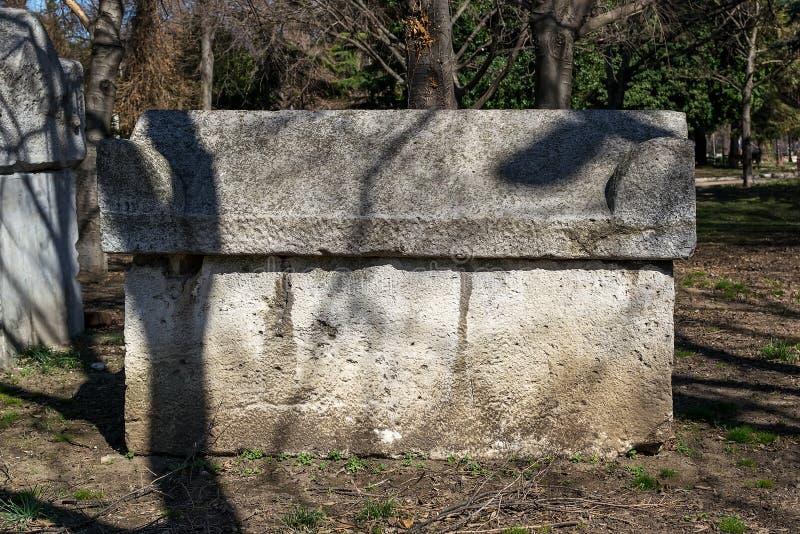 Sarcófago de pedra antigo no parque Os túmulos de pedra antigos são ficados situados em um parque público ao lado do museu arqueo imagens de stock