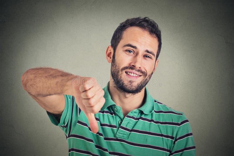 Sarcastic young man showing thumbs down sign hand gesture. Closeup portrait sarcastic young man showing thumbs down sign hand gesture, happy someone made mistake royalty free stock photos