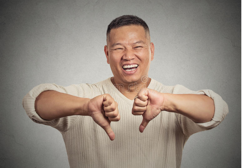 Sarcastic young man showing two thumbs down sign hand gesture. Closeup portrait sarcastic young man showing two thumbs down sign hand gesture, happy that someone stock image