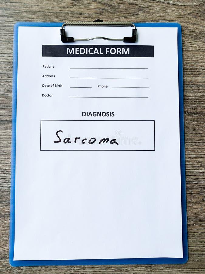 Sarcoma do diagnóstico em um formulário médico na mesa do doutor imagens de stock