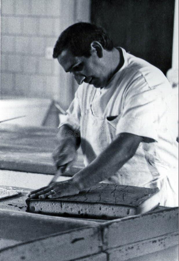 SARDEGNA, ITALIA, 1970 - el chef de repostería corta cuidadosamente una torta de esponja preparada en su taller fotos de archivo