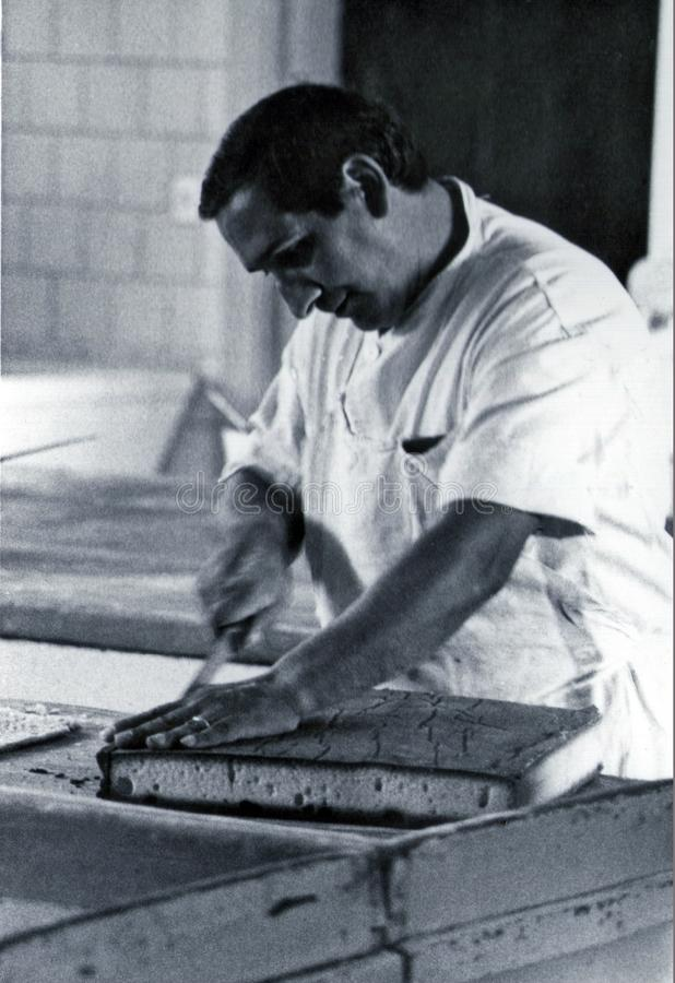 SARDEGNA, ITALY, 1970 - Pastry chef carefully cuts a sponge cake prepared in his workshop stock photos
