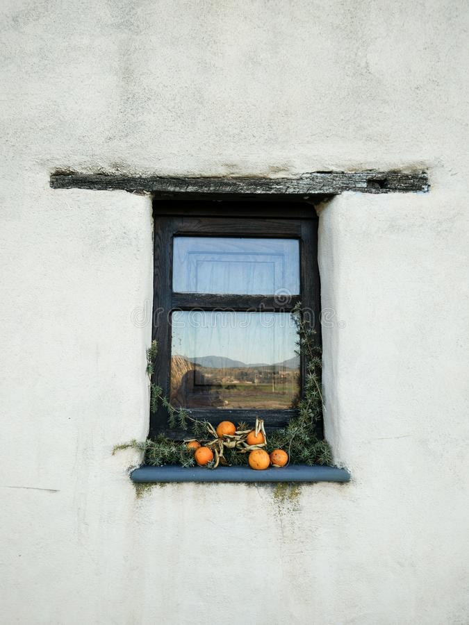 Sardina. Traditional architecture. The house. Details. Small window with wooden architrave and stone sill on white wall, decorated with dry oranges and branches stock images