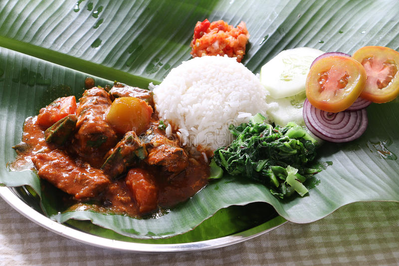 Sardine fish curry. South India cuisine, Sardine fish curry with tomato and Okra served with rice on banana leave royalty free stock image