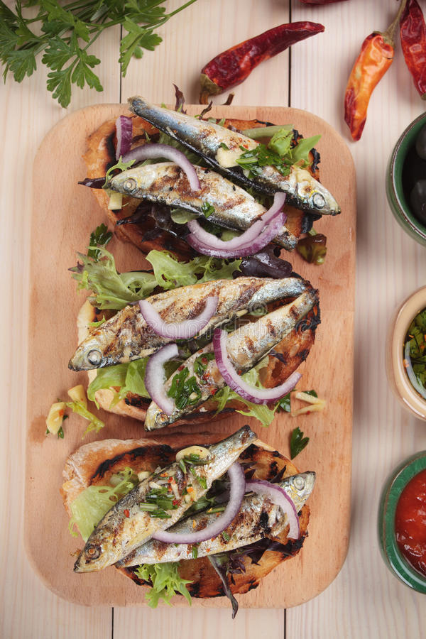 Sardine fish sandwich. Italian crostini sandwich with grilled sardine fish, lettuce and onion royalty free stock image