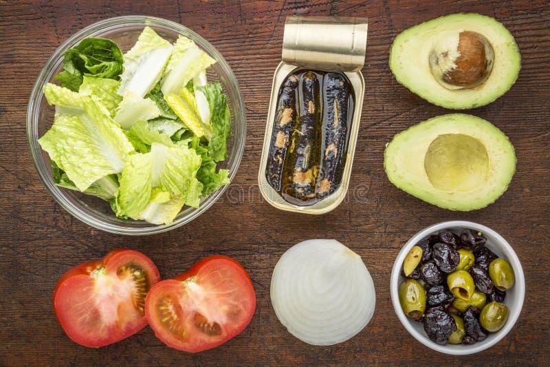 Sardine salad ingredients. Top view of sardine salad ingredients - romaine lettuce, tomato, onion, olives, avocado and canned sardines stock photo