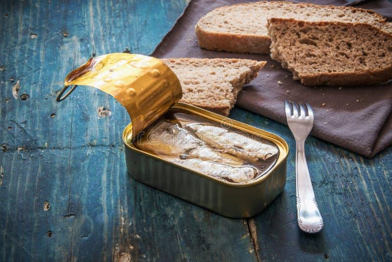 Sardiner i canen och skivorna av bröd på den blåa trätabellen royaltyfri fotografi