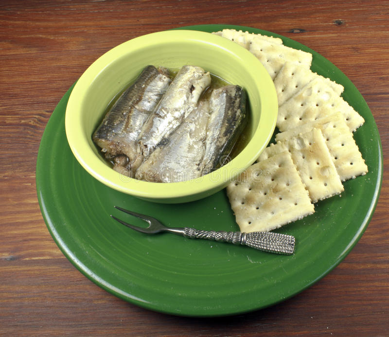 Sardines in a bowl. On a plate with crackers and serving fork stock photography