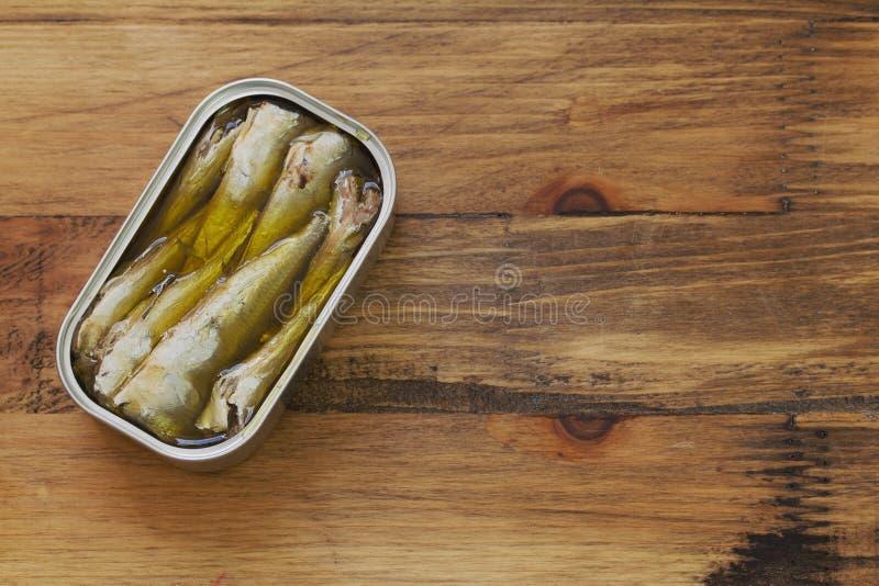 Sardines dans la boîte de fer sur le brun images stock
