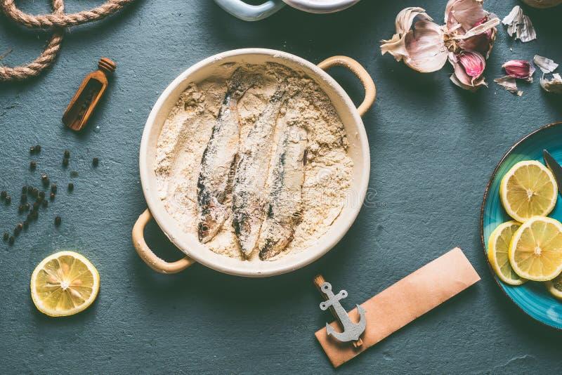 Sardines en miettes de pain sur le fond de table de cuisine avec des ingrédients : citron, ail et herbes pour la cuisson savoureu photos libres de droits