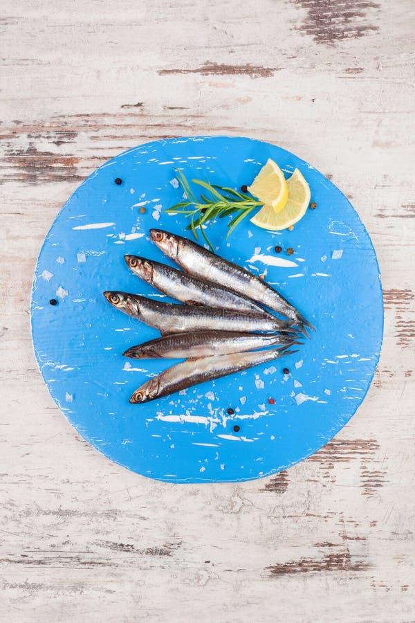 Sardines fraîches sur le panneau bleu de cuisine image libre de droits