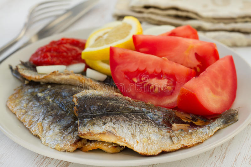 Sardines frites avec le citron image stock
