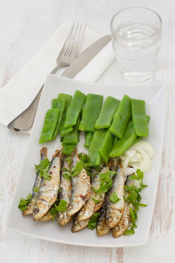 Sardines frites avec les haricots verts bouillis image libre de droits
