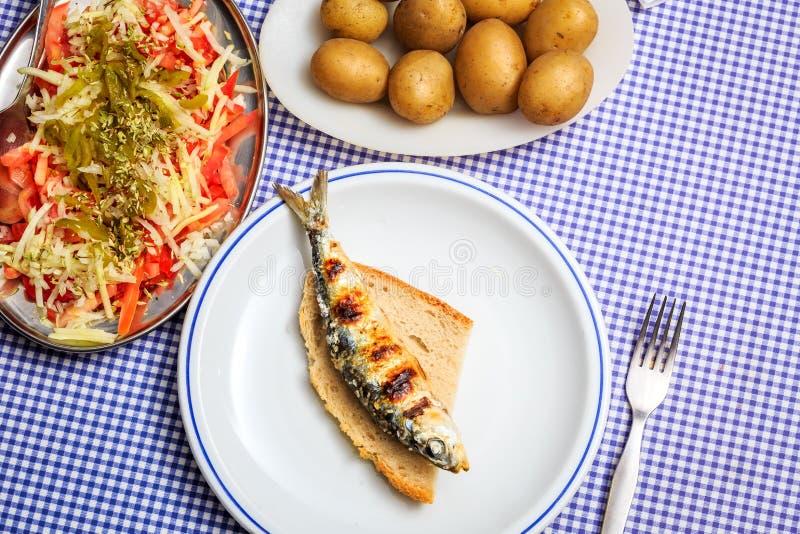 Sardines grillées avec de la salade, le pain et la pomme de terre images libres de droits