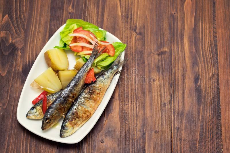 Sardines grillées avec la pomme de terre et la salade bouillies du plat blanc photos stock