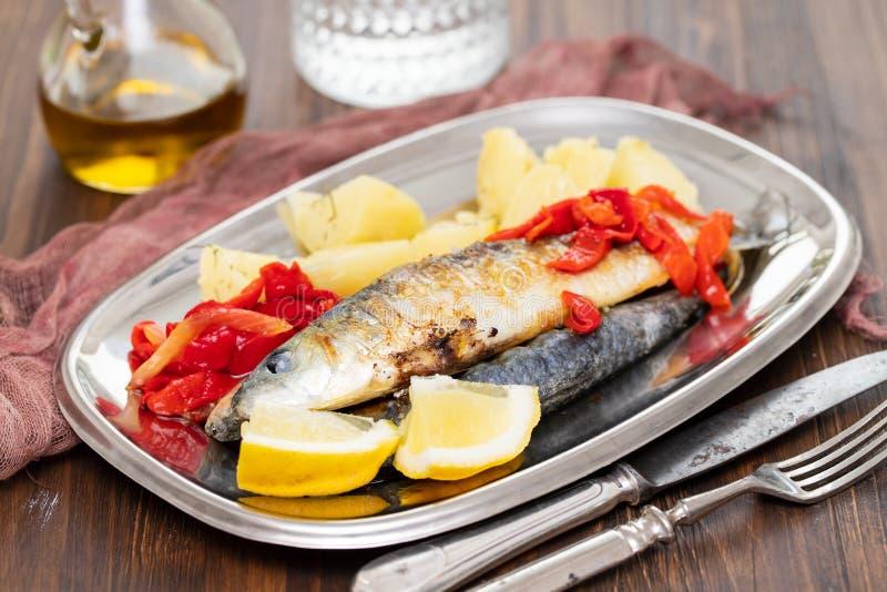 Sardines grillées avec le poivre et la pomme vapeur sur le plat photos stock