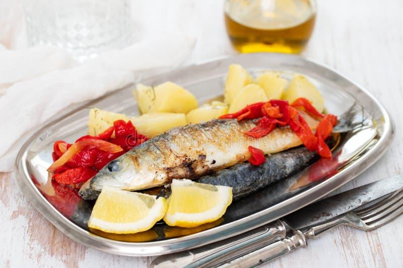 Sardines grillées avec le poivre et la pomme vapeur sur le plat photographie stock