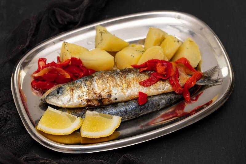 Sardines grillées avec le poivre et la pomme vapeur sur le plat photographie stock libre de droits