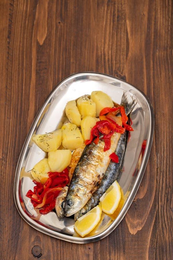 Sardines grillées avec le poivre et la pomme vapeur sur le plat photos libres de droits