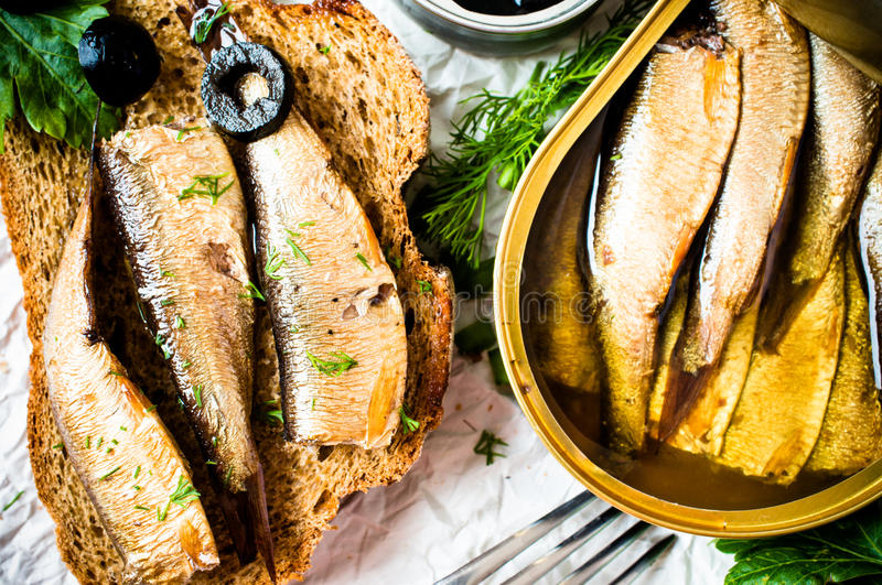 Sardines, sprats. Sandwich, tapas with sardines, sprats with olives and herbs royalty free stock photography