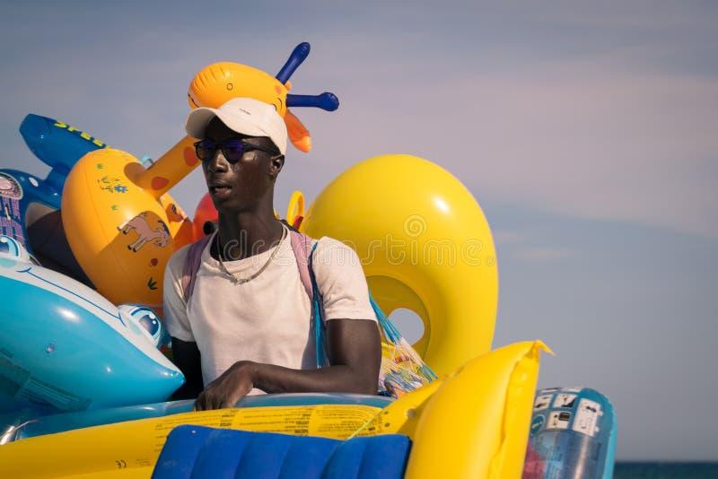 Vendor of water inflatable toys in Italian beaches. Sardinia, Italy - August 18, 2016: Street vendor of water inflatable toys in Italian beaches stock image