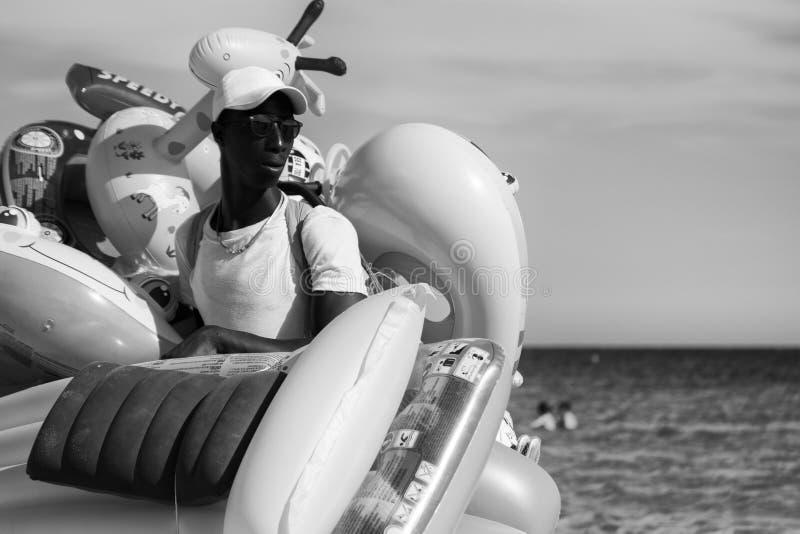 Vendor of water inflatable toys in Italian beaches. Sardinia, Italy - August 18, 2016: Street vendor of water inflatable toys in Italian beaches stock images