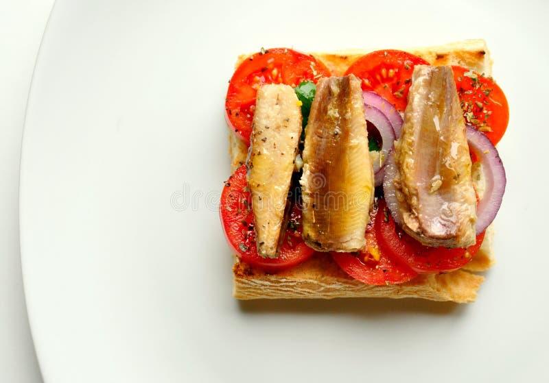 Sardynki ściskają z pomidorem na białym tle zdjęcie royalty free