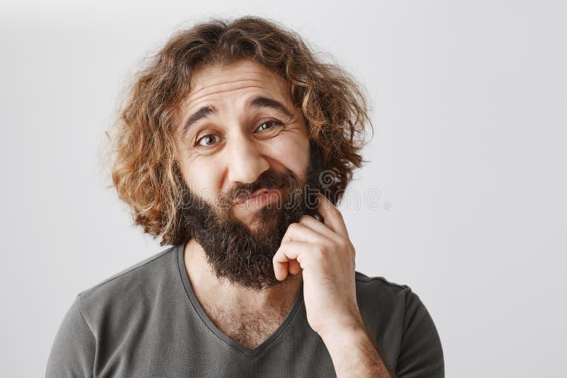 Sarebbe problematico Ritratto della barba orientale incerta di scratch dell'uomo di esitazione e sopracciglia di sollevamento con immagini stock libere da diritti