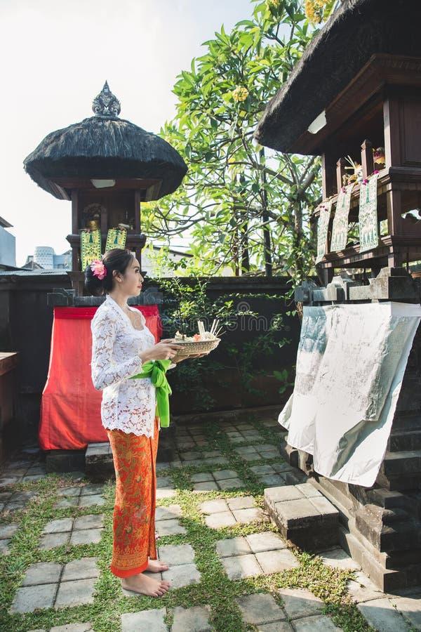 Sari del canang de la rogación y de las ofrendas de la mujer del Balinese en el templo en el SM fotografía de archivo