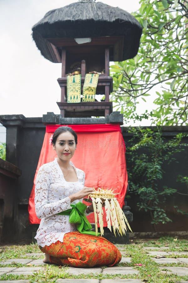 Sari del canang de la rogación y de las ofrendas de la mujer del Balinese en el templo en el SM fotos de archivo libres de regalías