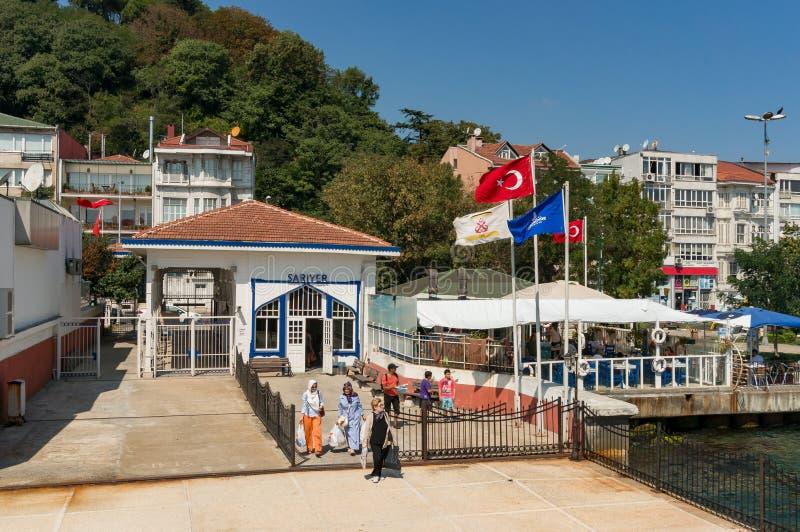 Sariyer promu nabrzeże z Tureckimi flagami państowowymi i ludźmi oczekuje abordaż obrazy royalty free