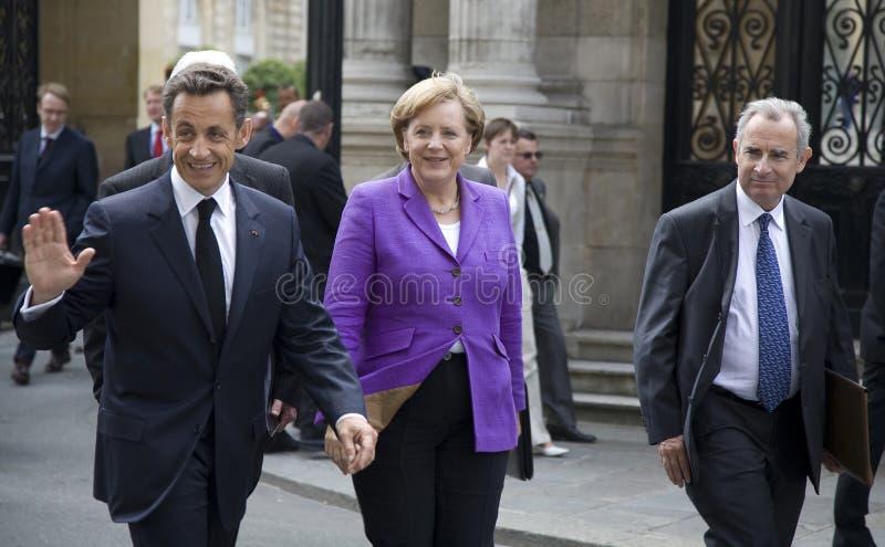 Sarkozy and Merkel. PARIS, FRANCE - JUNE 11 - 2009: French president Nicolas Sarkozy (waving) and German chancellor Angela Merkel (C) outside the Elysee Palace stock photography