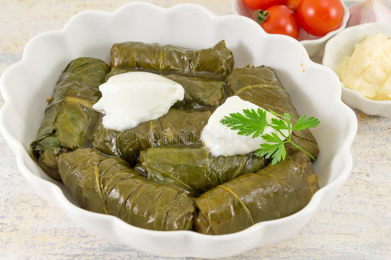 Sarma rolls in a plate covered with spices. And sour cream stock image